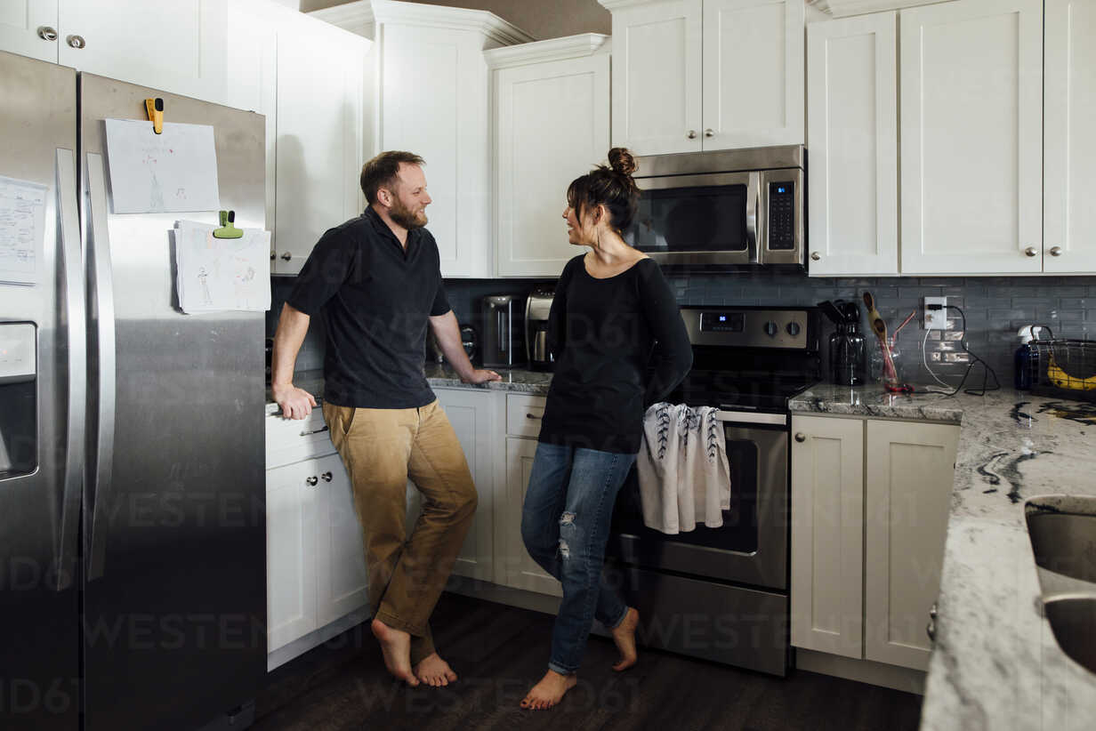 Couple talking while standing in kitchen at home