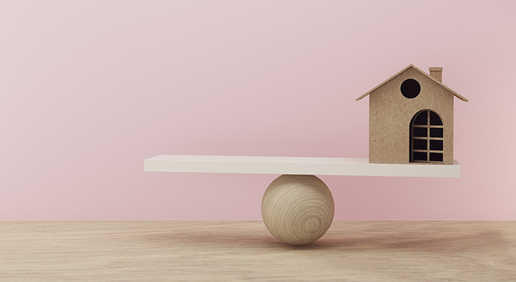 House a balance scale in equal position on wooden table and pink background. financial management, depicts short term borrowing for a residence.