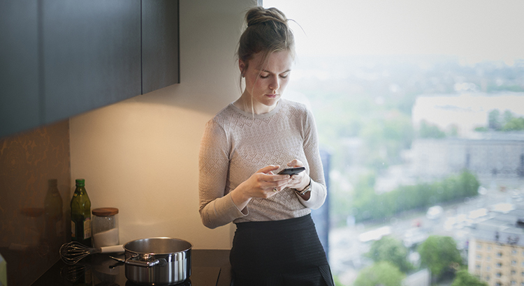 young woman in kitchen with smartphone