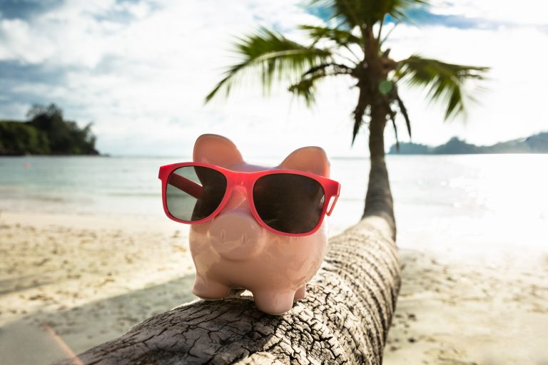 Close-up,Of,Pink,Piggybank,With,Sunglasses,On,Tree,Trunk,At